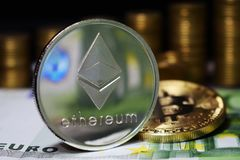 Coin physical Ethereum ETH on Euro banknote, background from golden coins Bitcoin. royalty free stock image