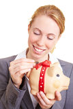 Coin into a piggy bank Royalty Free Stock Photo