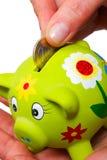 Coin in a piggy bank Stock Photos