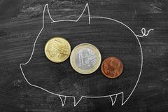 Coin into a piggy bank Stock Photos