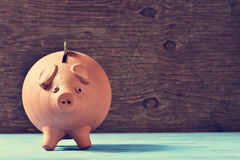 Coin in a piggy bank Royalty Free Stock Images