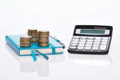 Coin pile, pocket calculator and notebook Stock Photos