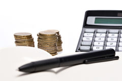Coin pile, pocket calculator and notebook Stock Image