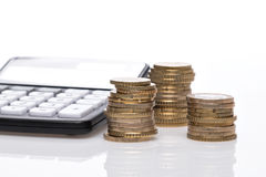Coin pile, pocket calculator and notebook Royalty Free Stock Photo