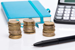 Coin pile, pocket calculator and notebook Royalty Free Stock Photography
