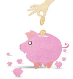 Coin into pink piggy bank with recycled pape Stock Photos