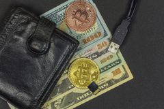 Coin purse with cash, two coins Bitcoin, flash drive and USB con. On a dark background lies a coin purse with cash, two Bitcoin coins, a flash drive and a USB Royalty Free Stock Photo