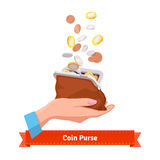 Coin rain to a purse in woman hand Stock Image