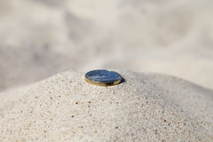Coin in sand. Royalty Free Stock Photography