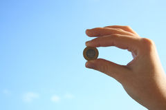 Coin on sky. Womans hand on a sky background Royalty Free Stock Image