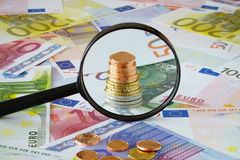 Coin stack behind magnifying glass. On a background made of Euro banknotes and coins Royalty Free Stock Photography