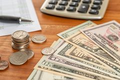 Coin stack with a calculator and dollar bills royalty free stock photography