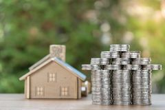 Coin stack with house model, savings plans for housing ,green background, financial concept royalty free stock images