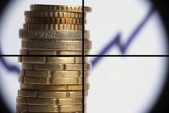 Coin stack with rising chart line, being aimed by a cross-sight scope. Stack pile of coins with rising chart line behind, being aimed by a cross sight scope Stock Photo
