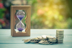 Coin stack on wood with sand clock. On wood stock images