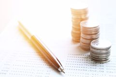 Coin stacks, pen and savings account passbook or financial statement on office desk table. Business, finance, saving money or investment concept : Coin stacks Stock Image