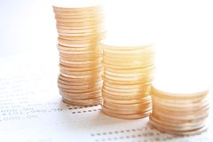 Coin stacks and savings account passbook or financial statement on office desk table. Business, finance, saving money or investment concept : Coin stacks and Royalty Free Stock Image