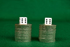 Coin stacks and two dices Stock Photo
