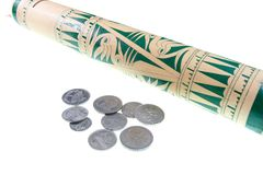 Coin and traditional bamboo tubes Stock Photo