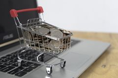Coin in a trolley on a laptop keyboard. Ideas about online shopping, online shopping is a form of electronic commerce that allows. Consumers to directly buy stock photo