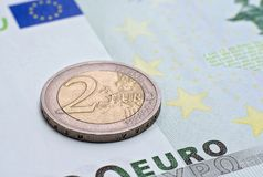 Coin two euros  on the banknote of hundred euro. Closeup Royalty Free Stock Photos