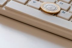 Coin in two pesos on the computer keyboard close-up. Online business in Argentina. International sales on the Internet. Copy space stock photos