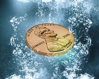 Coin under water. Money coin falling in blue water with bubbles Stock Photo