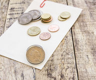 Coin on white paper on wooden table Stock Images