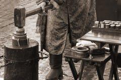 Coinagehantverkare som stämplar mynt med hammaren och städet Retro stilbegrepp arkivbild