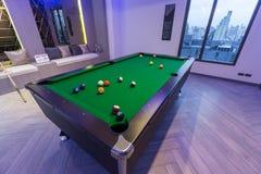 Coincez la table verte de billards de piscine avec l'ensemble complet de boules et de deux queues de poo dans une salle moderne d images stock