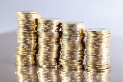 Coins. Four coin piles with reflection Stock Image