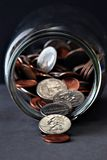 Coins. Spilling from a glass jar stock photo