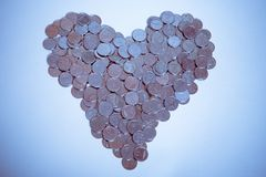 Coins. Heart arranged with coins in blue tone royalty free stock photo