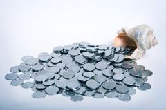 Coins. Pour out from nutshell in blue tone royalty free stock image