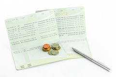 Coins on account passbook with pen isolate Royalty Free Stock Image
