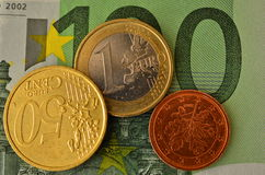 Coins against to 100 euro bill. Close up shot of small change against to 100 euro bill Royalty Free Stock Photography