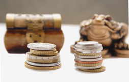 Coins against the wooden chest a Stock Photos