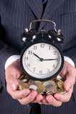 Coins and alarm stock image