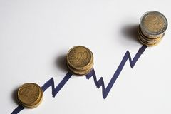 Coins along the rising peaks of a chart line. Overview Royalty Free Stock Images