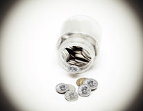 Coins of American currency coming out of Saving Jar Royalty Free Stock Photography