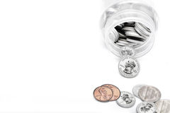 Coins of American currency coming out of Saving Jar Royalty Free Stock Photos
