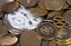 Coins and Antique pocket watch Royalty Free Stock Images