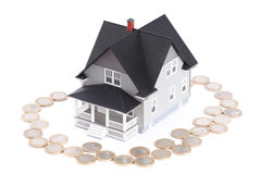 Coins around the home architectural model Stock Image