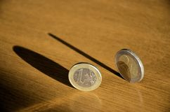 Coins in balance. Balanced coins with shadows on the table royalty free stock image