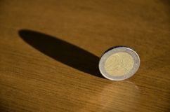 Coins in balance. Balanced coins with shadows on the table stock photos