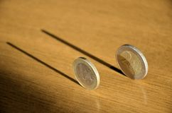 Coins in balance. Balanced coins with shadows on the table stock image