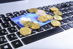 Coins and a bank card on the keyboard Stock Images