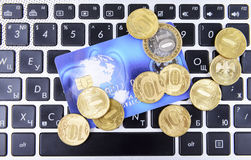 Coins and a bank card on the keyboard Stock Photography