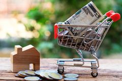 Coins and bank note in shopping cart with wooden house model aside. Property investment and home mortgage concept. Copy space royalty free stock photo