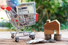 Coins and bank note in shopping cart with wooden house model aside. Property investment and home mortgage concept. Copy space royalty free stock images